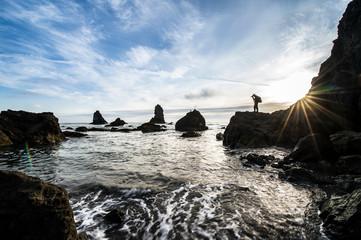 Photographer on rocky coastline during sunset