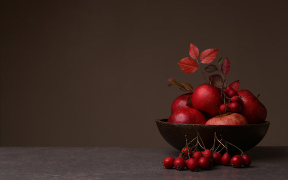 Background with hawthorn berries and apples in plate. Autumn composition of red berries and fruits with empty place.