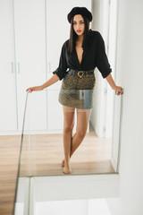 Stylish woman standing near glass railing