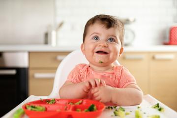 Smiling chubby baby eating brocoli