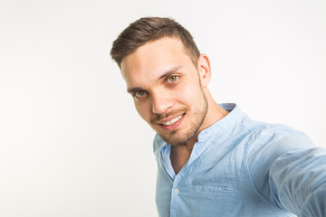 Close up portrait of a cheerful bearded man taking selfie over white background