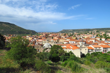 View over the old town of Bosa, the church and typical houses with red roofs surrounded by mountains and the Mediterranean Sea in the distance, Sardinia, Italy