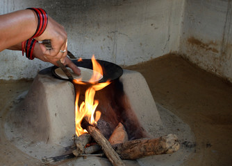 woman preparing chapati in traditional way on a wood fired oven