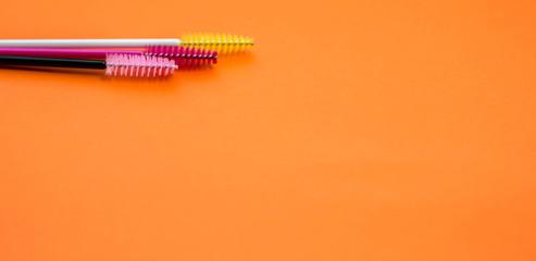 brushes for combing eyelash extensions isolated on orange background