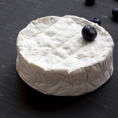 Camembert cheese with blueberries on dark background, side view. Food for wine. Milk production. Closeup.