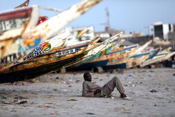 A man takes a break next to fishing boats in Dakar