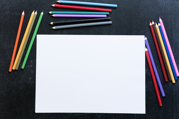 Blank paper list with coloured pencils around on black chalk table.