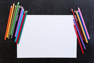 Blank paper list with coloured pencils on balck background.
