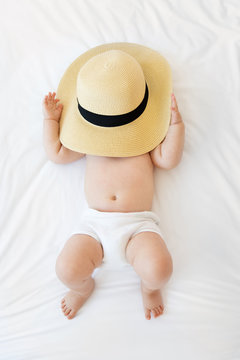 Chubby baby covering face with straw hat