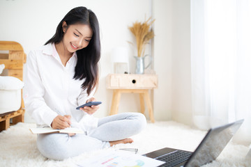 Happy casual beautiful woman working on a laptop and smart phone sitting in the bedroom Wall mural