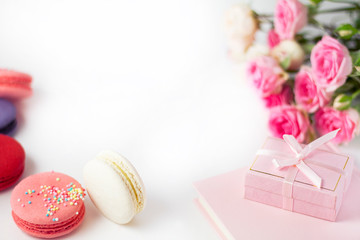 Multi-colored macaroons, flowers, gift box on a white background, suitable for a background.