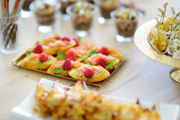Delicious salmon and raspberry mini bruschettas served on a party or wedding reception.