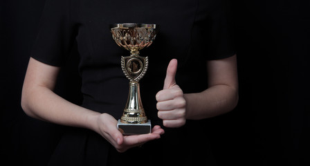 low key image of a woman holding a trophy cup over dark background. Award and Concept of Victory.