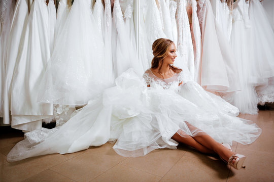 Back view of a young woman in wedding dress looking at bridal gowns