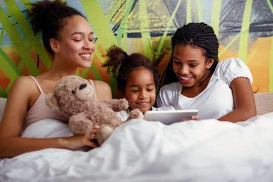Young mother lying in a bed with daughters and looking at digital tablet