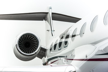 High detailed closeup view on small white private business jet windows engine