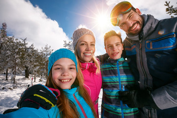 .family smiling and making selfie on winter ski vacation.