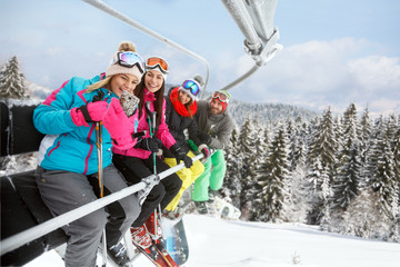 Woman in ski lift taking selfie with friends