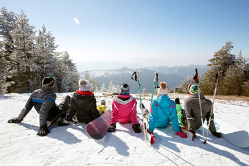 Skiers resting on snow from skiing, back view