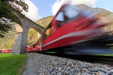 Train passing under the Brusio Spiral Viaduct in UNESCO landscape along the Bernina Railway Line. Val Poschiavo, Graubuenden, Switzerland.