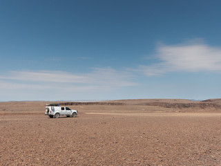 Offroad vehicle with rooftent in stone deset in the Ai-Ais Richtersveld Transfroniter Park in Namibia.
