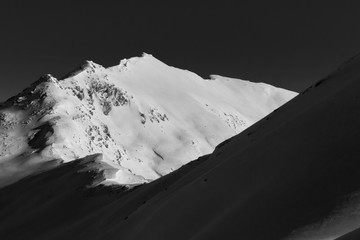 Black and white mountain peakc overed with snow in the Swiss Alps, Graubuenden, Switzerland.