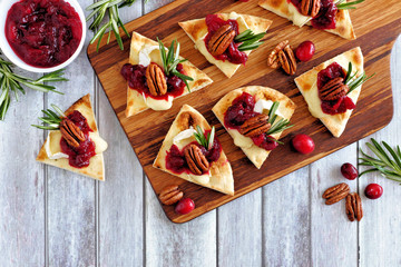 Spoed Fotobehang Voorgerecht Holiday flatbread appetizers with cranberries, pecans and brie cheese. Top view table scene on a wooden platter.