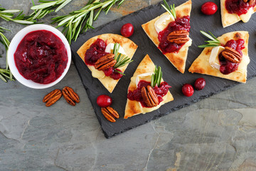 Holiday flatbread appetizers with cranberries, pecans and brie cheese. Above view scene on a dark slate background.