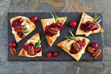 Holiday flatbread appetizers with cranberries, pecans and brie cheese. Top view on a dark slate platter.