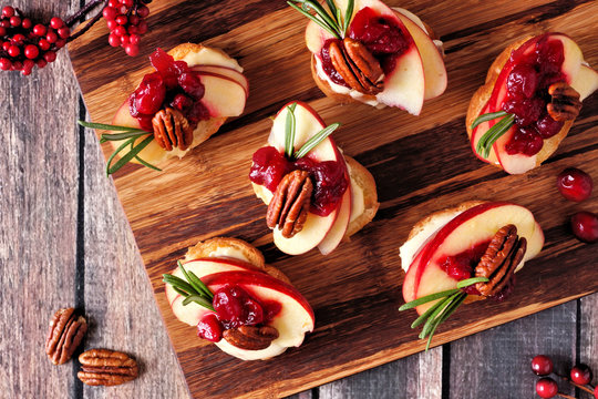 Crostini appetizers with apples, cranberries, brie and pecans. Top view on a dark slate background.