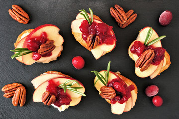 Spoed Fotobehang Voorgerecht Crostini appetizers with apples, cranberries, brie and pecans. Top view on a dark slate background.