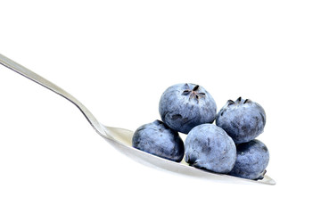 blue berry on spoon isolated on white background