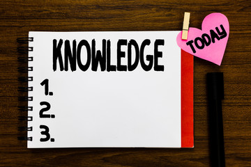 Conceptual hand writing showing Knowledge. Business photo text Facts information skills acquired through experience or education Open notebook page markers holding paper heart wooden background