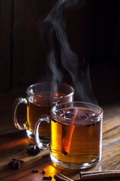 2 glass mugs of steaming hot spiced cider on dark wood