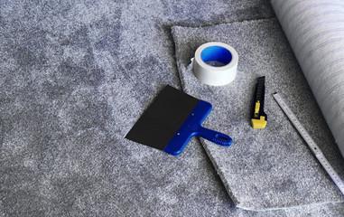 Die Verlegung von einem neuen grauen Teppichboden