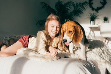 Beautiful young caucasian girl playing with her puppy beagle dog, sunny morning on bedroom