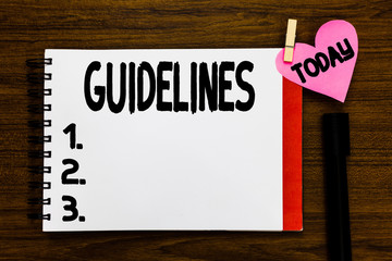 Conceptual hand writing showing Guidelines. Business photo text General rule principle piece of advice Policies Instructions Open notebook page markers holding paper heart wooden background