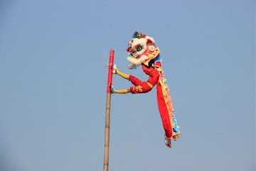 Chinese lion dance on the pole with the background of clear blue sky.