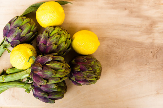 artichokes cooked with lemon and salt on rustic wooden background