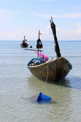 A small traditional wooden Asian fishing boat moored in a bay with a fisherman working in the ocean silhouetted in the background.