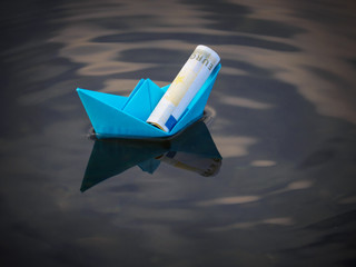 the ship is constructed of blue paper on Board which lies a twisted Euro banknote floating on the water