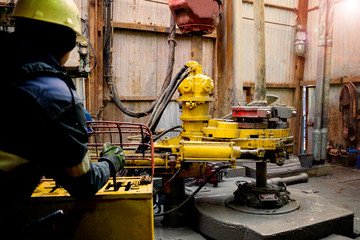 Offshore oil rig worker prepare tool and equipment for perforation oil and gas well at wellhead platform. Making up a drill pipe connection. A view for drill pipe connection from between the stands.