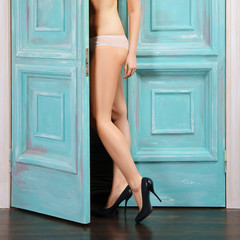 Bare female legs in high heel shoes near open door