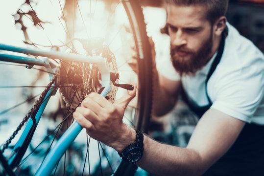 Handsome Bike Mechanic Repair Bicycle in Workshop