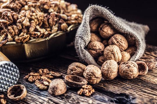 Walnut kernels whole walnuts in burlap sack and vintage bowl