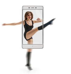 Young beautiful ballet dancer training on white background. conceptual image with a smartphone, demonstration of device capabilities