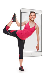 Young fit smiling woman doing stretching exercise with raised leg, concept virtual reality of the smartphone. going out of the device