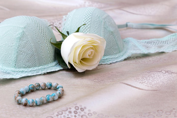 Light green push up bra with a white rose and a turquoise bracelet on soft beige cloth