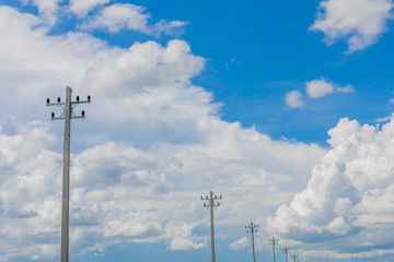 Electrical pole in blue sky background and white cloud.