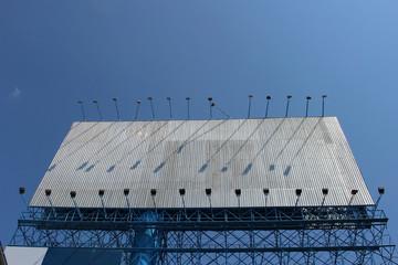 Big blank steel advertising billboard against a blue sky background